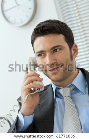 Young businessman talking on landline phone at office, smiling. - stock photo