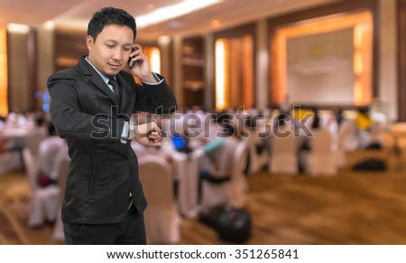 Young businessman talking on mobile phone and looking at watch on Abstract blurred photo of conference hall or seminar room with attendee background, business concept - stock photo