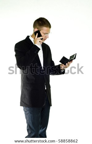 Young businessman talking on mobile while holding a black, leather wallet, isolated on white background