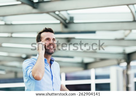 Young businessman talking on phone outside the office - stock photo