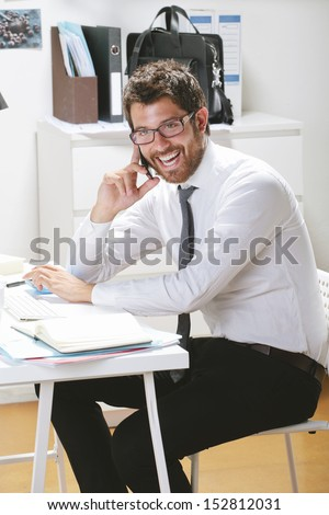 Young businessman talking on smart phone in office. Businessman with rimmed glasses working.
