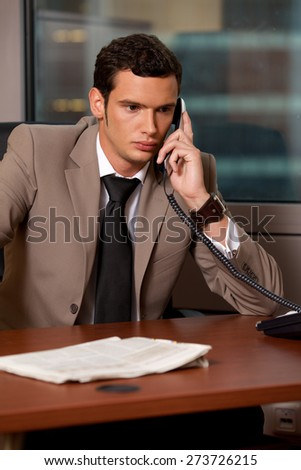 Young businessman talking on telephone in office