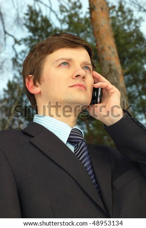Young Businessman talking on the cell phone outdoors - stock photo