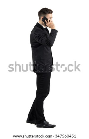 Young businessman talking on the cell phone walking side view. Full body length portrait isolated over white studio background.  - stock photo