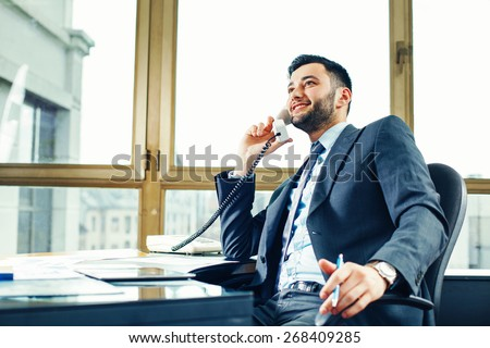 Young businessman talking on the phone at the office - stock photo