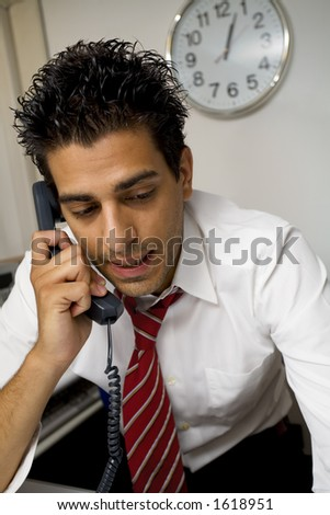 young businessman talking on the phone in his office - stock photo