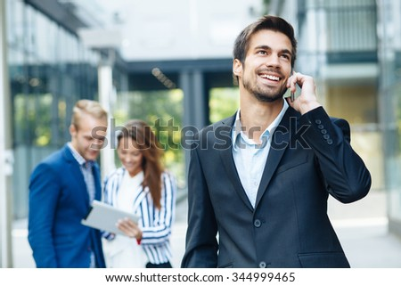 Young businessman talking on the phone. Selective focus on the man in front. Toned image - stock photo