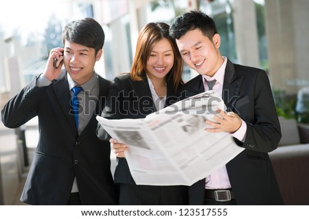 Young businessman talking on the phone while his associates reading newspaper - stock photo