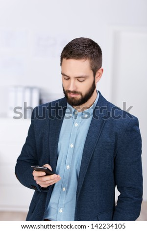 Young businessman text messaging through cell phone while standing in office - stock photo