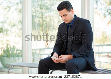Young businessman texting and social networking with his smart phone at work - stock photo