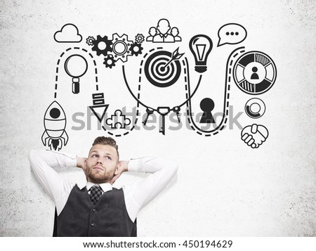 Young businessman thinking about new business ideas on concrete background with sketch. Startup concept
