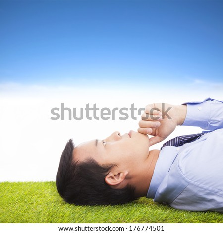 young businessman thinking   and contemplating on a meadow - stock photo