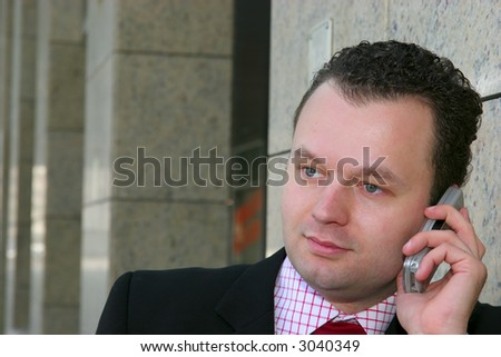 Young businessman thinking and talking on a cell phone in front of a corporate building - stock photo