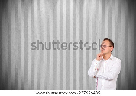 young businessman thinking on a concrete wall - stock photo