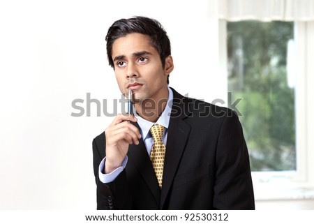 Young businessman thinking with serious expression - stock photo