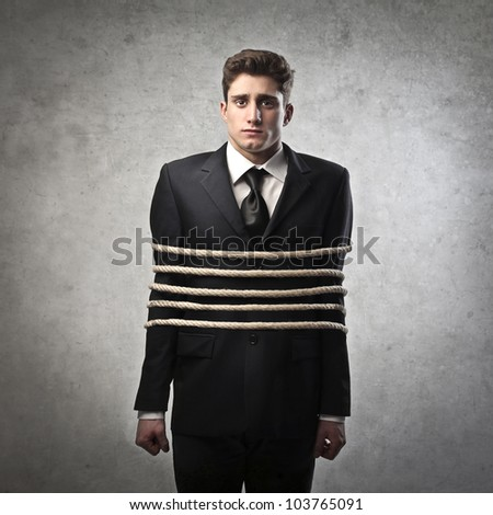 Young businessman tied with ropes - stock photo