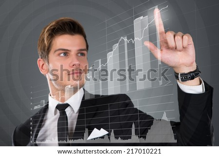 Young businessman touching transparent screen with growing bar graph over gray background - stock photo