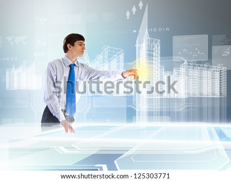 young businessman toucning high-tech image of building model - stock photo