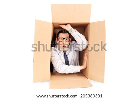 Young businessman trapped in a box isolated on white background - stock photo
