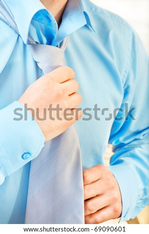 Young businessman tying a tie - stock photo