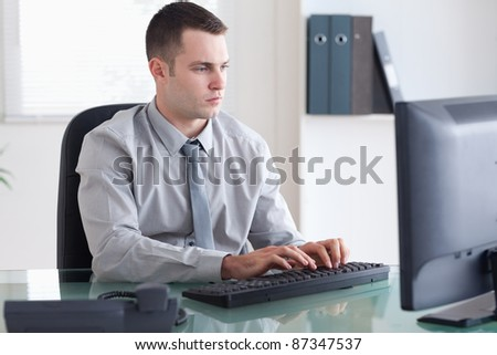 Young businessman typing on his computer