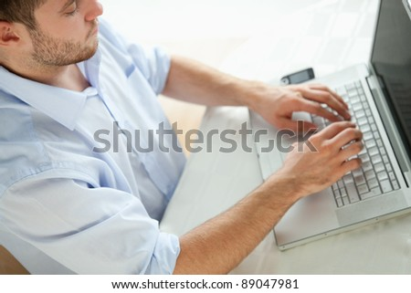 Young businessman typing on laptop - stock photo
