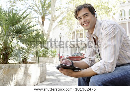 Young businessman using a cell phone's ear piece to speak on the phone while sitting down on a bench in the city.
