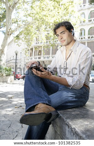 Young businessman using a cell phone's ear piece to speak on the phone while sitting down on a step in the city.
