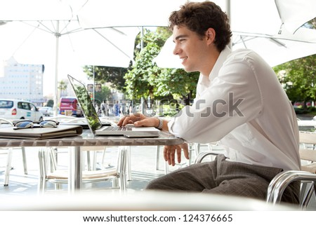 Young businessman using a laptop computer while sitting at a coffee shop terrace table under a parasol, outdoors. - stock photo