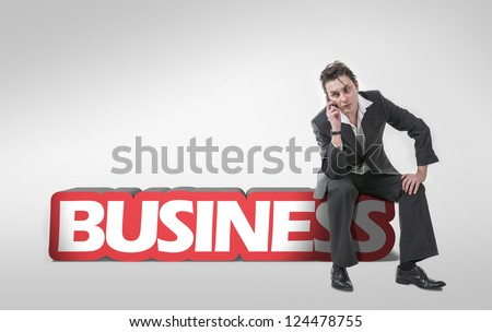 Young businessman using a mobile phone and sitting on 3d text