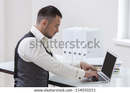 Young businessman using at laptop at desk - stock photo