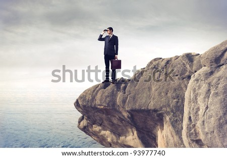 Young businessman using binoculars from a rock over the sea - stock photo