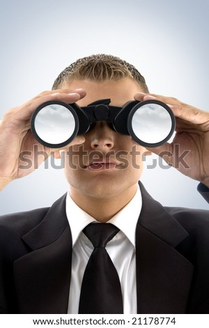 young businessman using binoculars looking at the sky - stock photo