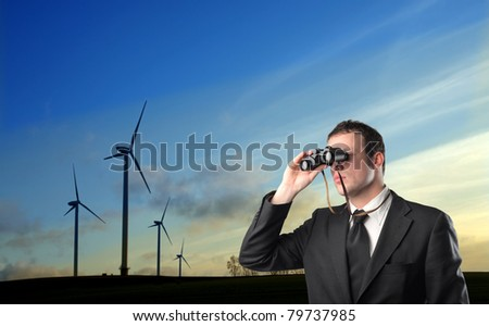 Young businessman using binoculars with windmills in the background - stock photo