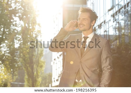 Young businessman using cell phone outdoors - stock photo