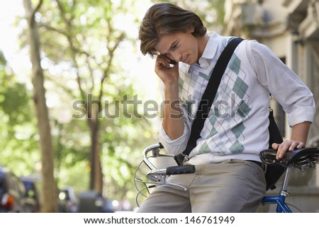 Young businessman using cell phone while sitting on bicycle outdoors - stock photo