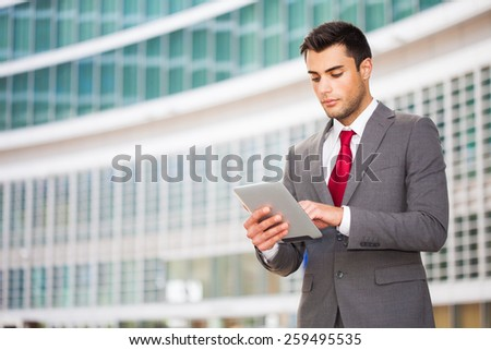 Young businessman using his digital tablet - stock photo