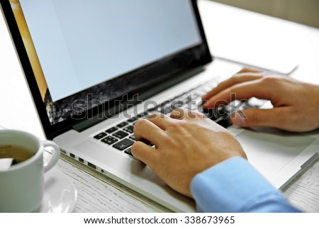 Young businessman using his laptop, close up - stock photo