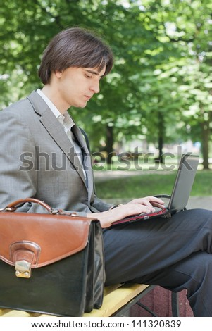 young  businessman using his laptop in park