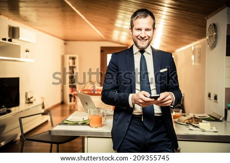 Young businessman using his mobile phone at home during breakfast - stock photo