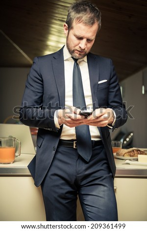 Young businessman using his mobile phone at home during breakfast