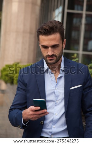 Young businessman using his mobile phone on the street - stock photo
