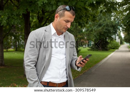 Young businessman using his phone and walking in a street - stock photo