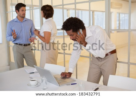 Young businessman using laptop and cellphone with colleagues in background at the office - stock photo