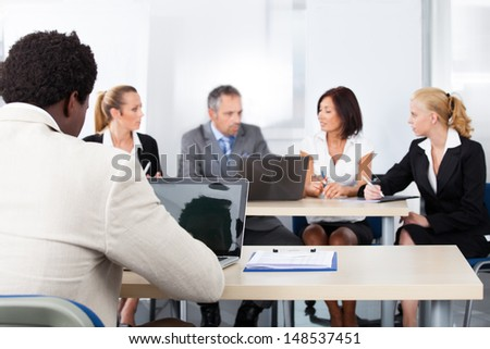 Young Businessman Using Laptop In Front Of His Colleagues In Office - stock photo