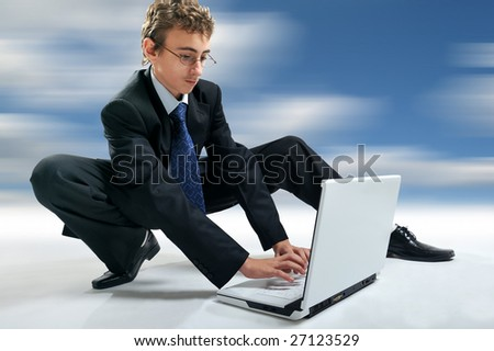 Young businessman using laptop in unusual position, abstract background - stock photo