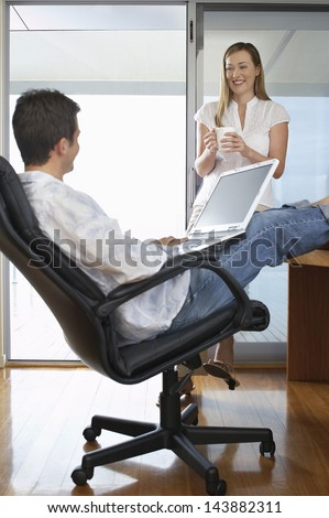 Young businessman using laptop with woman holding coffee cup in home office
