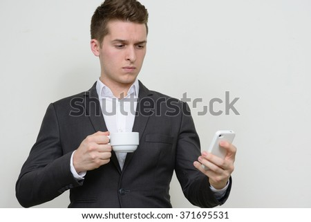 Young businessman using mobile phone and holding coffee cup