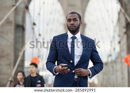 Young businessman using mobile phone on Brooklyn Bridge. New York City. - stock photo