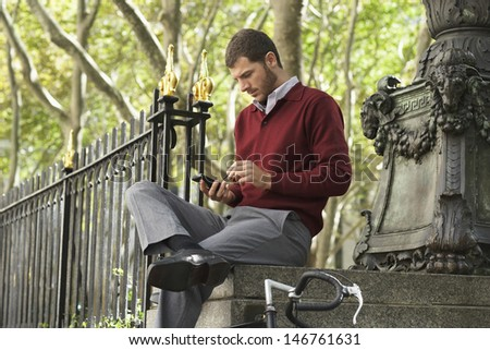 Young businessman using smartphone while sitting on wall outdoors - stock photo
